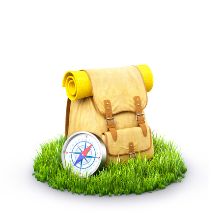 Backpack with  compass  on grass at white background. Unusual travel background