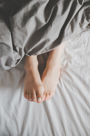 Soft photo of womans feet under a blanket, top view point Stock Photo