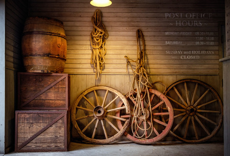 Old cart wheels, boxes and wine barrel.
