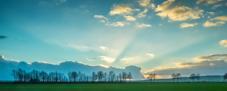 sunrise mountain: Scenic panorama of green field at sunset Stock Photo