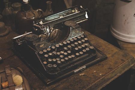 metal grunge: Vintage typewriter machine on wooden table. Closeup photo