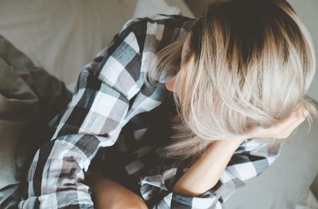 mujer triste: Foto suave de la mujer en camisa de cuadros sobre la cama, punto de vista superior