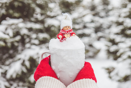 snow tree: Woman in red gloves is holding the mug with snow and cute christmas toy inside.