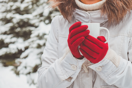 red gloves: Young woman in red gloves is holding the cup of tea in her hands
