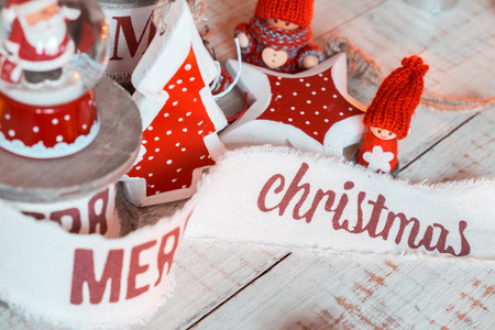 gnomos: Beautiful vintage christmas ribbons and toys on the wooden table. Cute and pleasant decorations in rustic style Foto de archivo