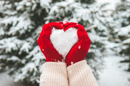 Woman in red gloves holds snow in hands in shape of heart.