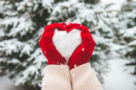 Mujer en guantes rojos sostiene nieve en las manos en forma de corazón. Foto de archivo
