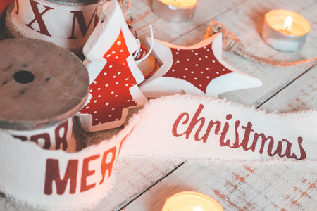 mo�os de navidad: Beautiful vintage christmas ribbons and toys on the wooden table. Cute and pleasant decorations in rustic style Foto de archivo