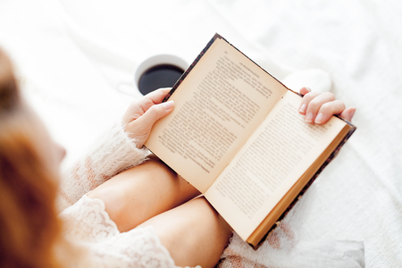 legwarmers: Soft photo of woman reading a book on the bed Stock Photo