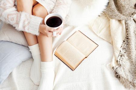 昔の本と一杯のコーヒー、最高のビュー ポイントとベッドの上の女性の柔らかい写真