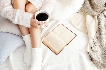 Soft photo of woman on the bed with old book and cup of coffee, top view point Imagens