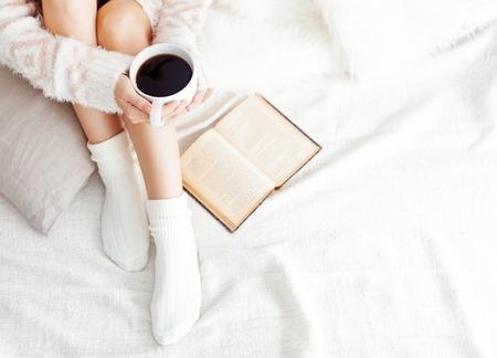 Zachte foto van de vrouw op het bed met oude boek en een kopje koffie, bovenaanzicht punt