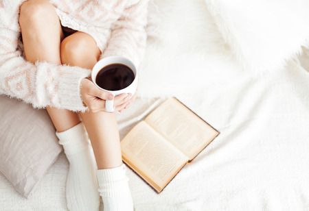 legwarmers: Soft photo of woman on the bed with old book and cup of coffee, top view point Stock Photo