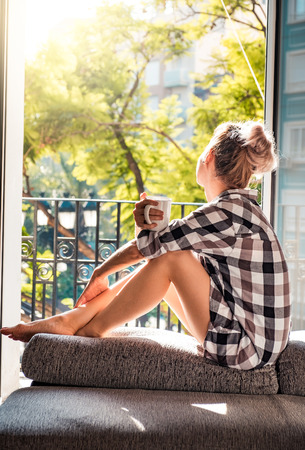 Genç güzel kadın açılan pencerede otururken kahve içme ve dış görünümlü dinlenme sahiptir
