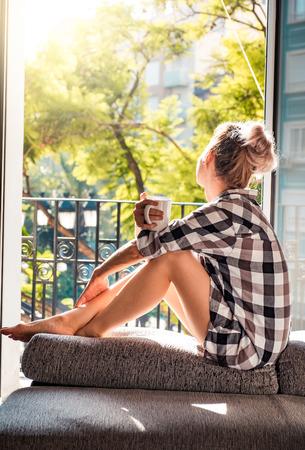 Mujer bonita joven sentado en la ventana abierta de beber café y mirando fuera goza de descanso Foto de archivo