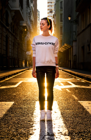 street light: Young stylish woman with closed eyes stands on the road at sunset. Stock Photo