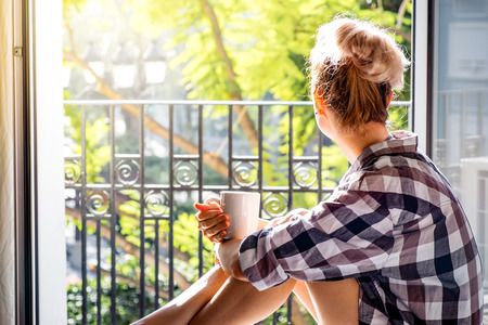 Młoda piękna kobieta siedzi przy otwartym oknie picia kawy i patrząc na zewnątrz cieszy odpoczynku Zdjęcie Seryjne