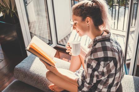 Giovane donna graziosa seduta alla finestra aperta bere il caffè e la lettura di un libro gode di riposo
