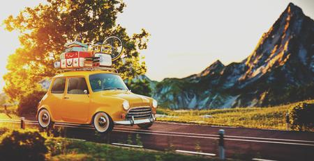 pequeño coche retro lindo con las maletas y bicicletas en la parte superior va por el camino maravilloso paisaje al atardecer Foto de archivo