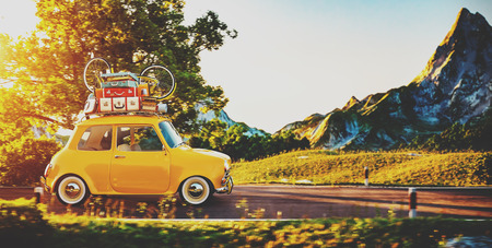 baggage: Cute little retro car with suitcases and bicycle on top goes by wonderful countryside road at sunset