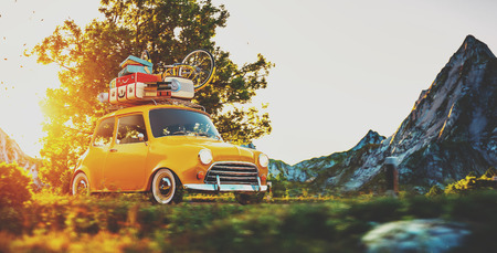 trips: Cute little retro car with suitcases and bicycle on top goes by wonderful countryside road at sunset