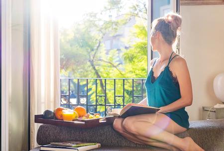 Giovane donna graziosa seduta alla finestra aperta bere caffè e guardando fuori gode di riposo Archivio Fotografico - 55257512