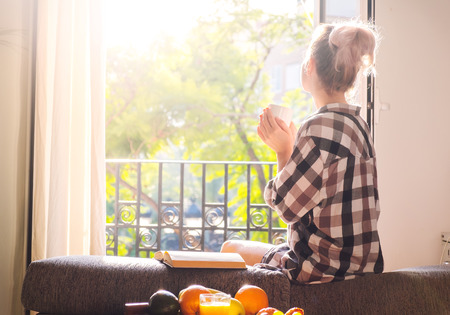 Young pretty woman  sitting at opened window drinking coffee and looking outside enjoys of rest Standard-Bild