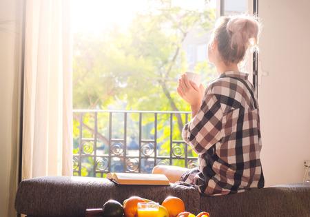 mujeres elegantes: Mujer bonita joven sentado en la ventana abierta de beber café y mirando fuera goza de descanso Foto de archivo