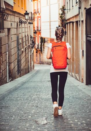 mochila de viaje: Muchacha turística con mochila está caminando por la calle