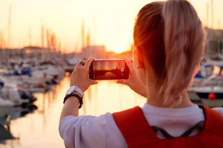 looking at camera: Young pretty girl is taking a picture of a bay with yachts at sunset