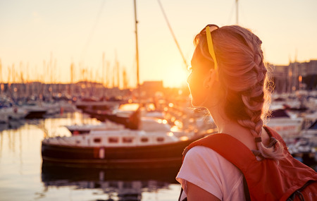 people travelling: Young pretty girl is standing on a pier and looking at the bay with yachts at sunset Stock Photo