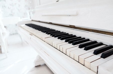 White vintage piano in a white room Stock Photo