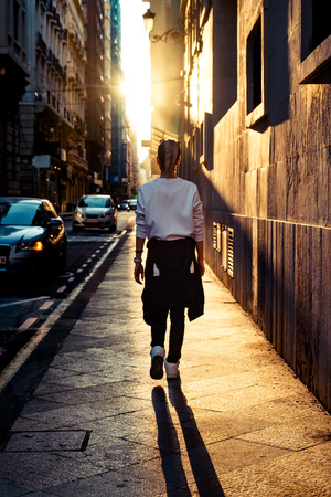 personas en la calle: estilo de la mujer joven caminando por la carretera en la calle al atardecer. Foto de archivo