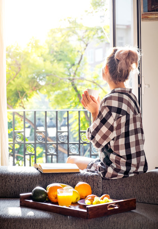 Young pretty woman  sitting at opened window drinking coffee and looking outside enjoys of rest Zdjęcie Seryjne