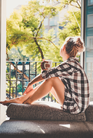 sitting pretty: Young pretty woman  sitting at opened window drinking coffee and looking outside enjoys of rest Stock Photo