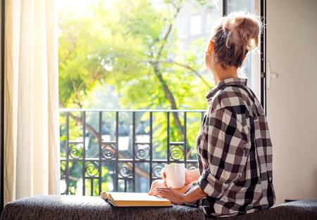 Young pretty woman  sitting at opened window drinking coffee and looking outside enjoys of rest 스톡 콘텐츠