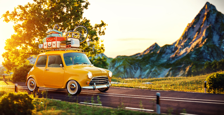 touring car: Cute little retro car with suitcases and bicycle on top goes by wonderful countryside road at sunset