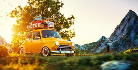 Schattige kleine retro auto met koffers en fiets op de top gaat door een prachtig landschap weg bij zonsondergang Stockfoto