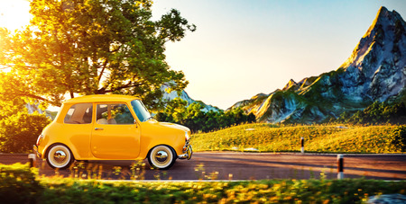 scenic drive: Cute little retro car goes by wonderful countryside road at sunset