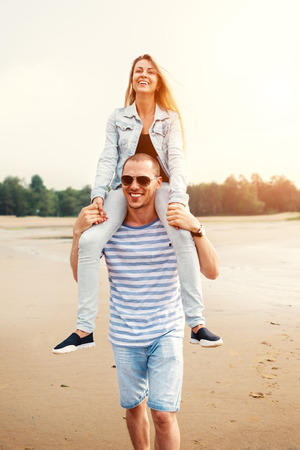shoulders: Young happy couple in love walking by the beach at summer sunset. Man Carrying girlfriend on Shoulders. Happy young family have a fun. Travel and vacation concept. Stock Photo