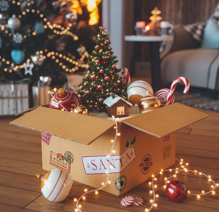 Opened gift box full of christmas  toys and cute little house from santa standing on a floor near christmas tree and fireplace in decorated interior. Unusual christmas 3d illustration Reklamní fotografie