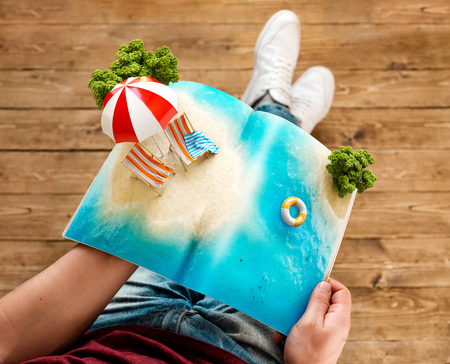 Tropical island with beach umbrella and deck chairs on a pages of opened magazine in hands. Unusual travel 3d illustration. Summer travel and vacation concept 스톡 콘텐츠