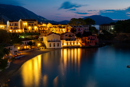 water town: Long exposure of the cute old town at the seaside at sunset with boats in the bay. Nice smooth reflection of city lights on water surface. Kefalonia Greece