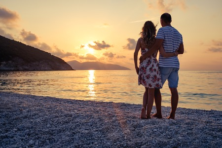 resting: Young couple in love standing on the beach at the seaside enjoying romantic evening and watching sunset. Family have a rest on the beach in summer. Stock Photo