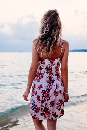 Beauty young woman in stylish dress standing on the beach at sunset over the horizon and looking away. Travel and vacation concept.