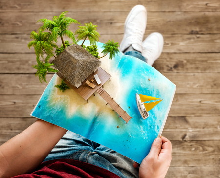 3d bungalow: Tropical island with bungalow and pier on a page of opened magazine in hands. Unusual travel 3d illustration. Summer vacation concept