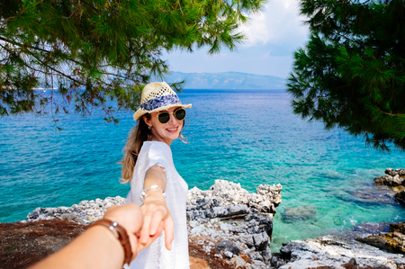 european: Beauty young woman in white clothes, straw hat and sunglasses holding man by hand and walking down to the beach at the seaside in sunny summer day. Travel and vacation concept. Follow me Stock Photo