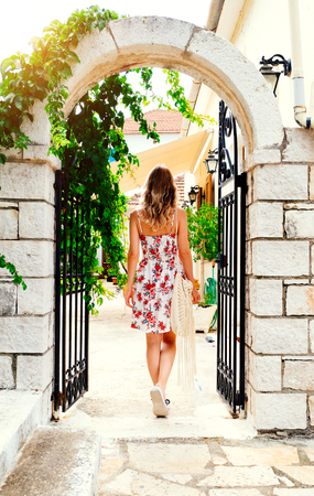 Beauty young woman in stylish dress walking by old european town at sunset over. Travel and vacation concept. Greece