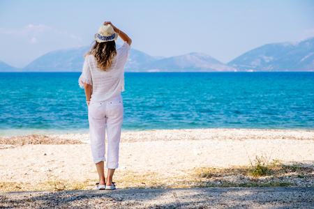 resting: Beauty tanned and stylish young woman in white clothes and straw hat enjoys her vacation standing at the beach in sunny summer day and looking away. Travel and vacation concept. Stock Photo