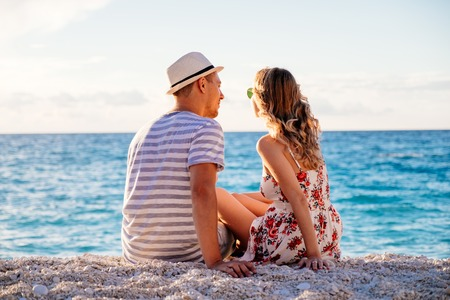 Young couple in love sitting on the beach at the seaside enjoying romantic evening and watching sunset. Family have a rest on the beach in summer.